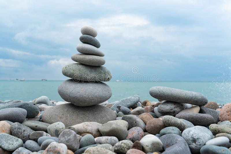 Stack of white pebbles stone against blue sea background for spa, balance, meditation and zen theme stock photos