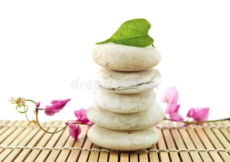 Stack of white stones. With green leaf and flower royalty free stock image
