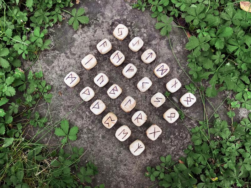 A stack of wooden runes at forest. Wooden runes lie on a rock background in the green grass. Runes are cut from wooden stock photography