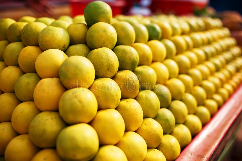 A stack of yellow ripe and sweet lines on the whole screen on the market. Lime and lemons background. Fresh organic lemons and royalty free stock images