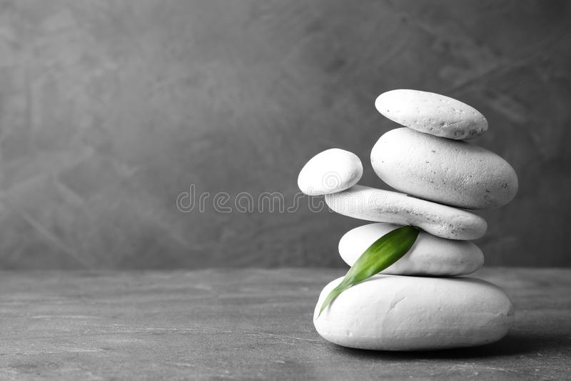 Stack of zen stones and bamboo leaf on table against grey background. Space for text royalty free stock photo