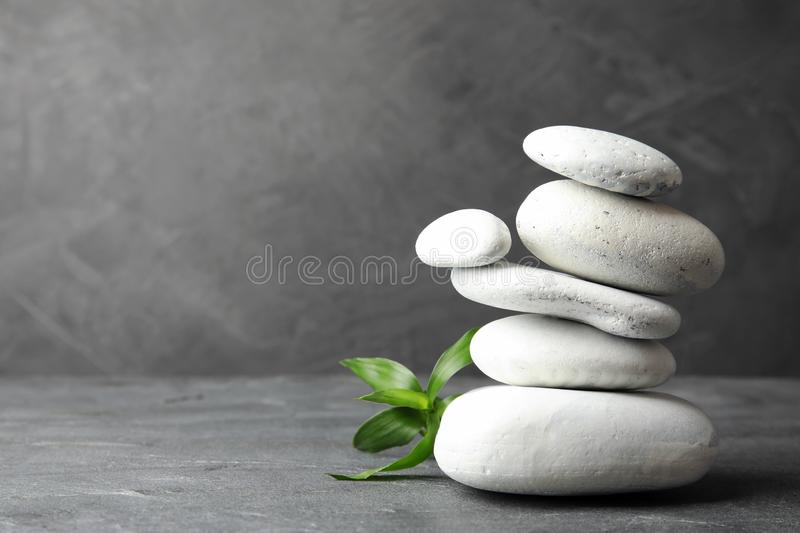 Stack of zen stones and bamboo leaves on table against grey. Space for text. Stack of zen stones and bamboo leaves on table against grey background. Space for stock photos