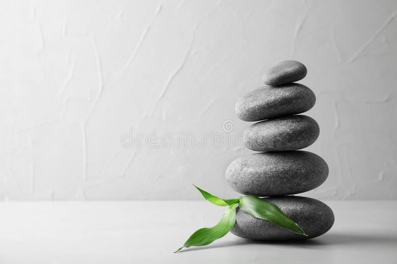 Stack of zen stones and bamboo leaves on table against light background. Space for text royalty free stock images