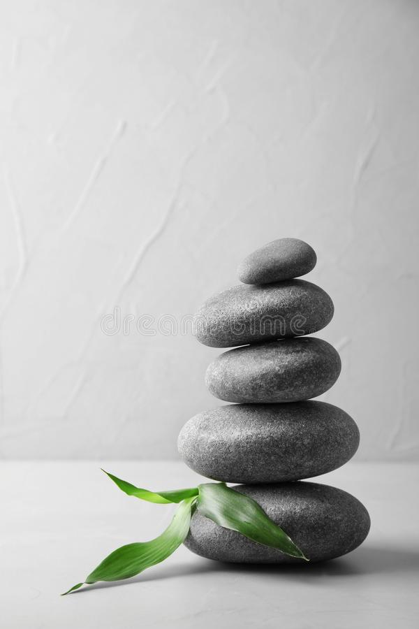 Stack of zen stones and bamboo leaves on table against light background. Space for text stock image