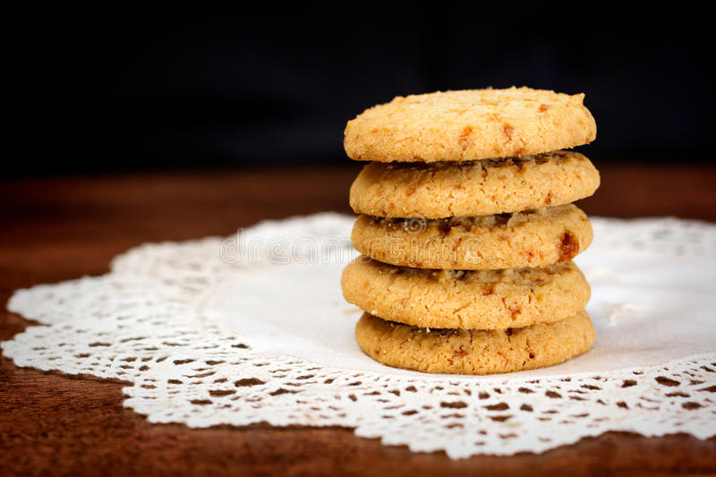 Stacked apple chip cookies on white napkin. Close up of stacked apple chip cookies on white rustic napkin with wooden background stock photo