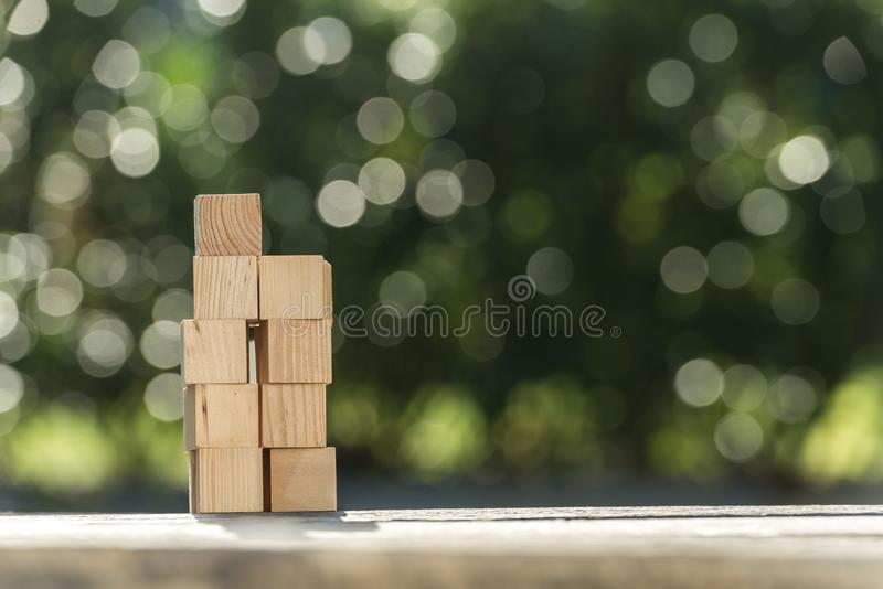 Stacked blank wooden toy blocks on a garden table. Outdoors against green with sparkling bokeh of sunlight in a conceptual image stock image