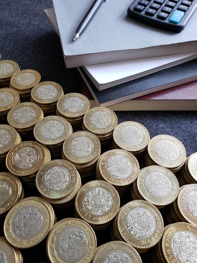 Free Stacked Books, Calculator, Pen And Mexican Coins Of Ten Pesos Royalty Free Stock Image - 146203616