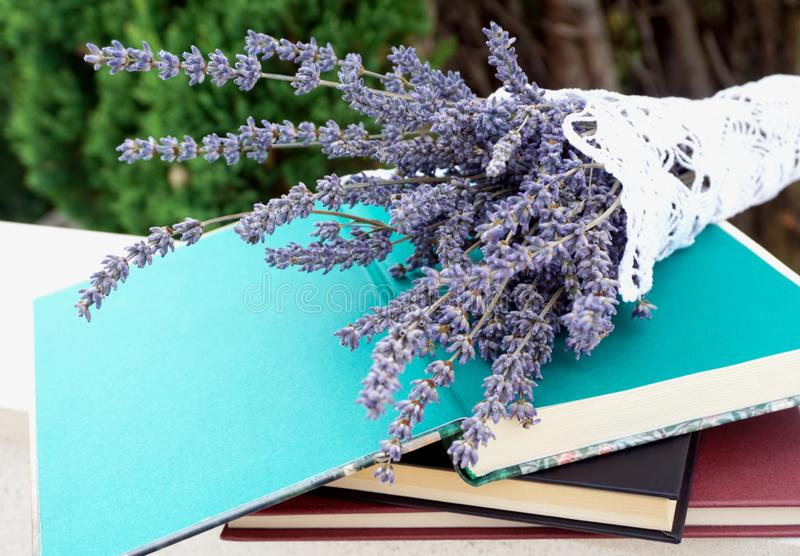 Stacked books and on the top open book decorated with bunch of lavender royalty free stock photos