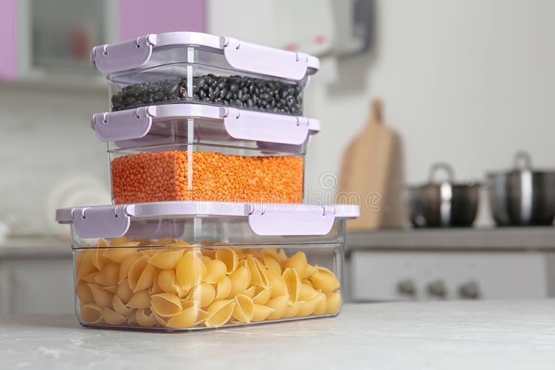 Stacked boxes with different food on table in kitchen. Space for text stock photography