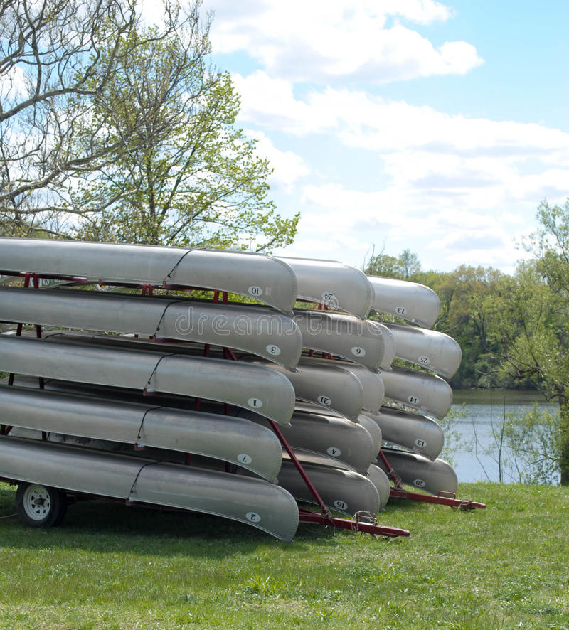 Stacked Canoes. On a trailer near a lake stock image