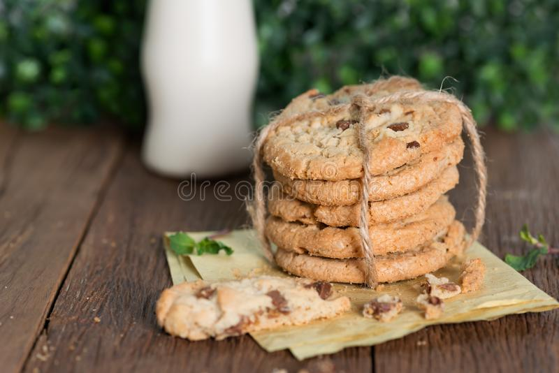 Stacked chocolate chip cookies with milk bottle on wooden table. royalty free stock photography