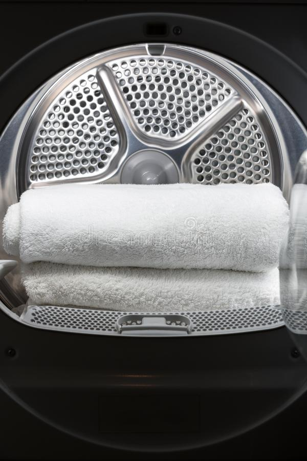 Stacked clean white towels inside washing machine drum. Clean concept. Laundry. Closeup of open washing machine stock photos