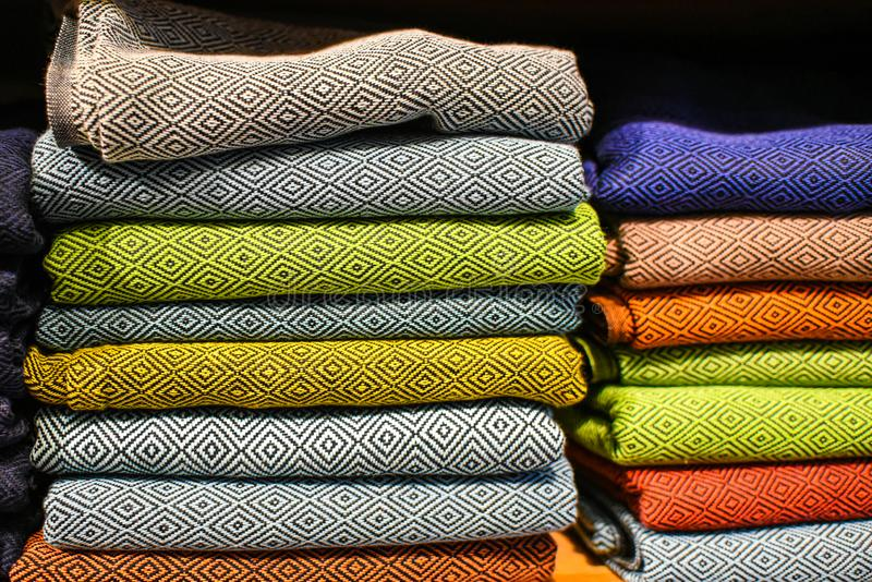 Stacked in the closet on the shelf colorful fabric clothes stock images