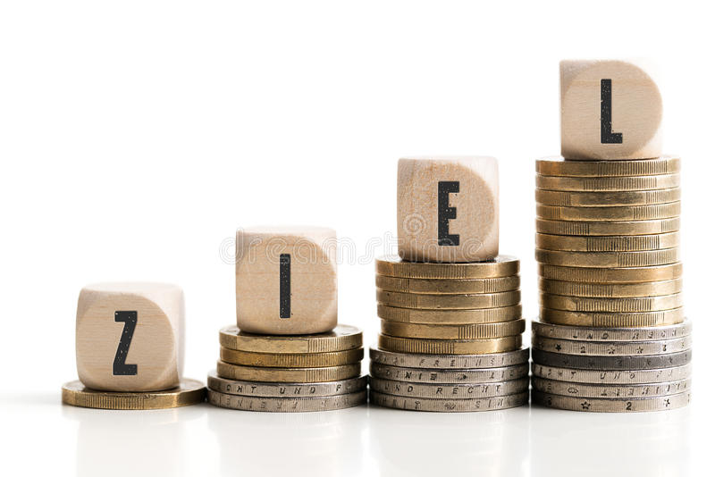 Stacked coins showing a growing graph with cubes and the German word `target` royalty free stock images