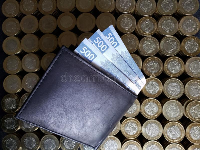 stacked coins of ten mexican pesos and black leather wallet with banknotes of 500 pesos stock images