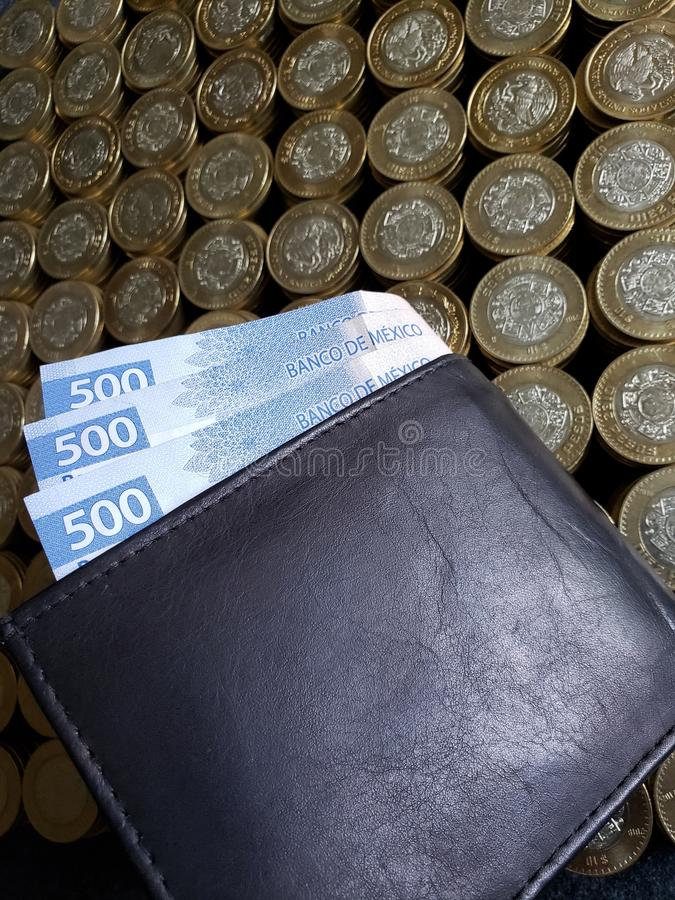 stacked coins of ten mexican pesos and black leather wallet with banknotes of 500 pesos stock photography