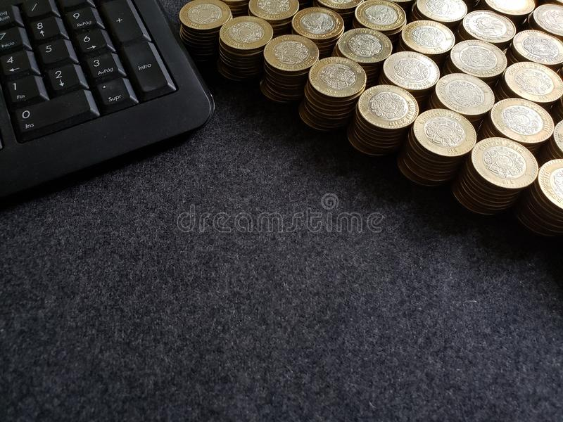 Stacked coins of ten mexican pesos and computer numeric keypad. Trading and exchange, bank and commerce, price of buy and sell, cash value and money, economy and stock image