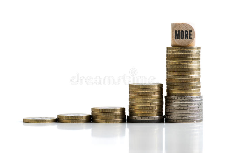 Stacked coins with the word `more` symbolizing greed stock photo