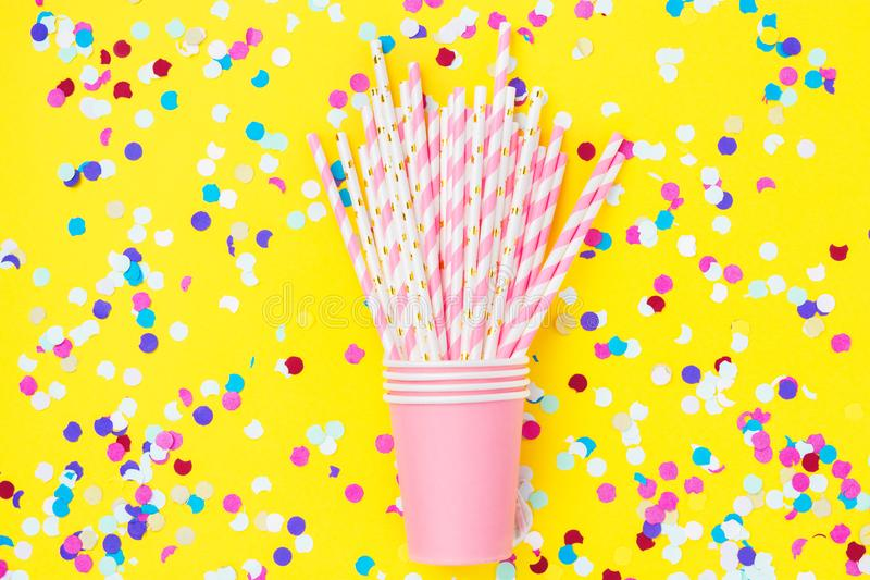Stacked drinking paper cup striped straws colorful confetti scattered on bright yellow background. Flat lay composition birthday stock photography