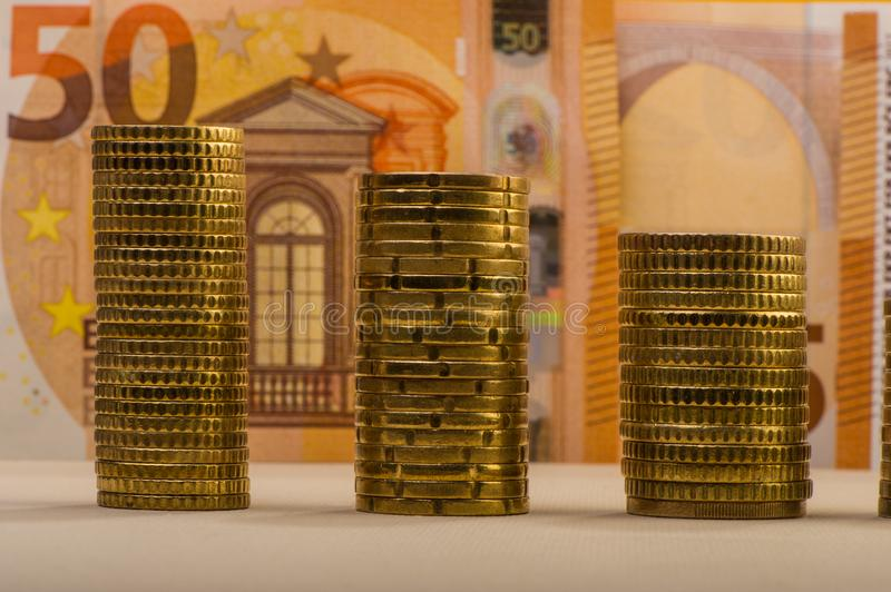 Stacked euro coins against a paper denomination worth fifty euro royalty free stock image