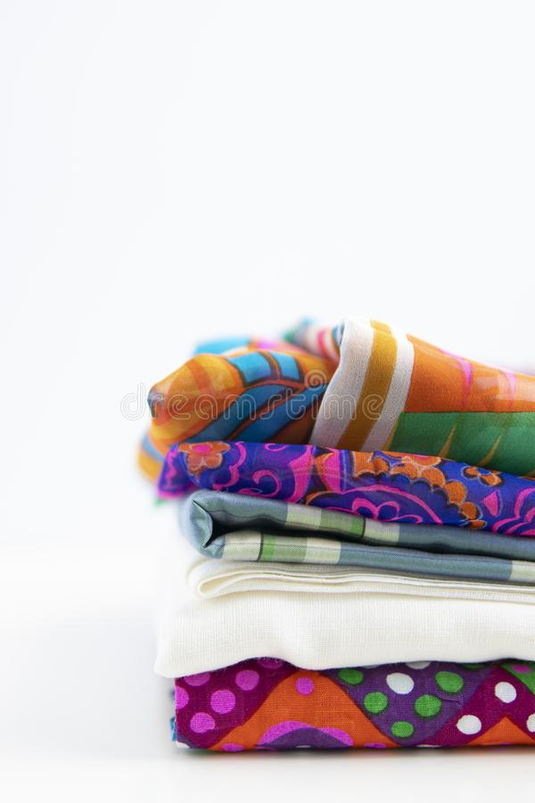 Stacked fabrics with vivd colors and patterns. stock photos
