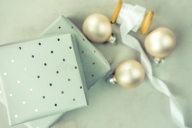 Stacked gift boxes wrapped in grey silver paper with polka dots pattern. Wooden spool with white silk ribbon, Christmas balls. royalty free stock images