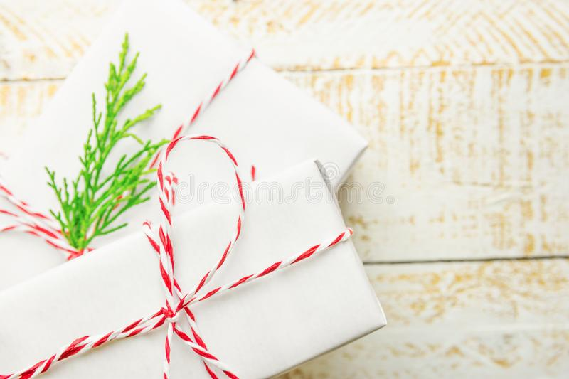 Stacked gift boxes wrapped in white paper tied with striped red ribbon green juniper twig on plank wood background. Christmas stock image