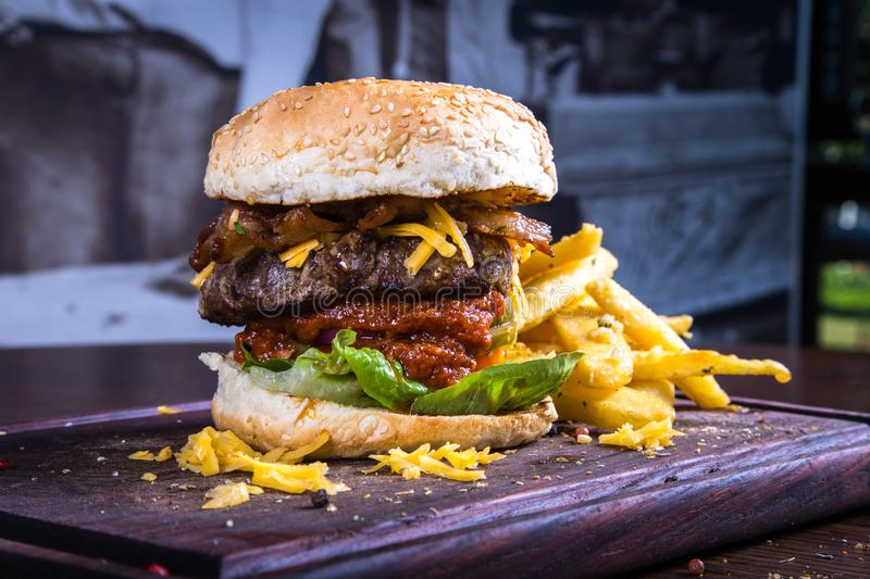 Stacked Hamburger and French Fries on Wooden Board. Large hamburger containing beef, cheese, bacon, lettuce and relish with a side of french fries stock image
