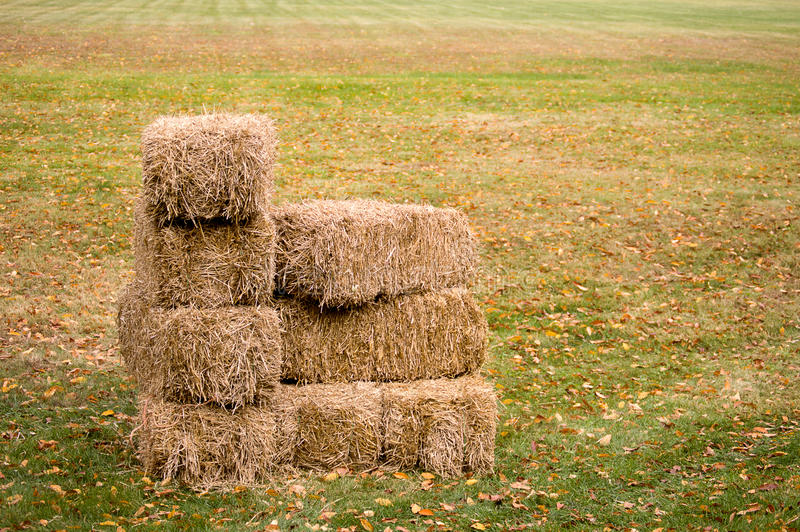 Stacked Hay Bales. On a field background stock photo