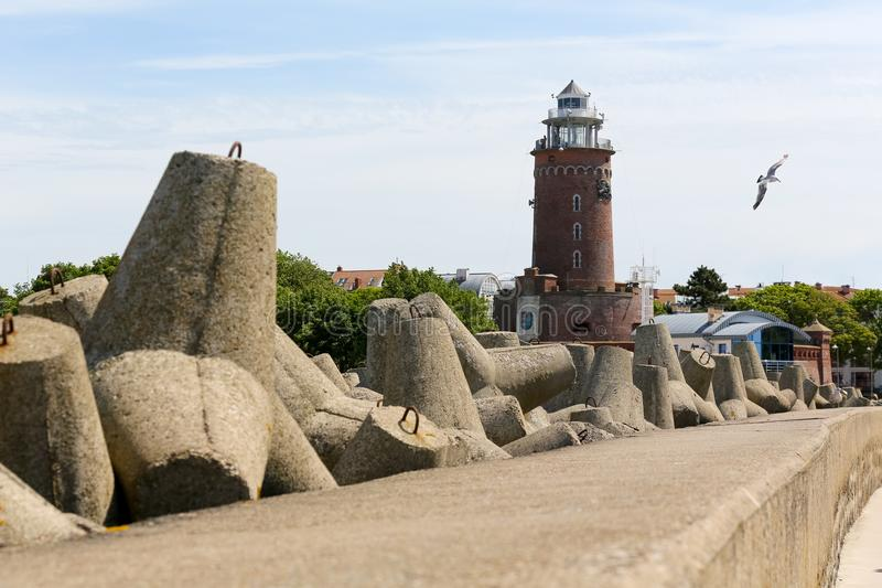 Stacked huge concrete blocks and lighthouse stock photos