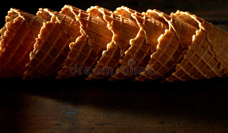 Stacked ice cream waffle cones on shadowy wood royalty free stock photos