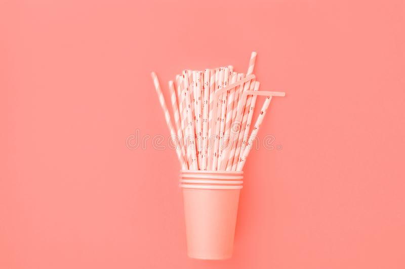 Stacked Pink Drinking Paper Cups with Striped Straws on Trendy Living Coral Color Background. Flat Lay Composition. Birthday Party Celebration Fashion Vacation royalty free stock image