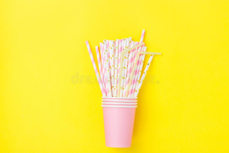 Stacked Pink Drinking Paper Cups with Striped Straws on Yellow Background. Flat Lay Composition. Birthday Party Celebration Kids royalty free stock photography