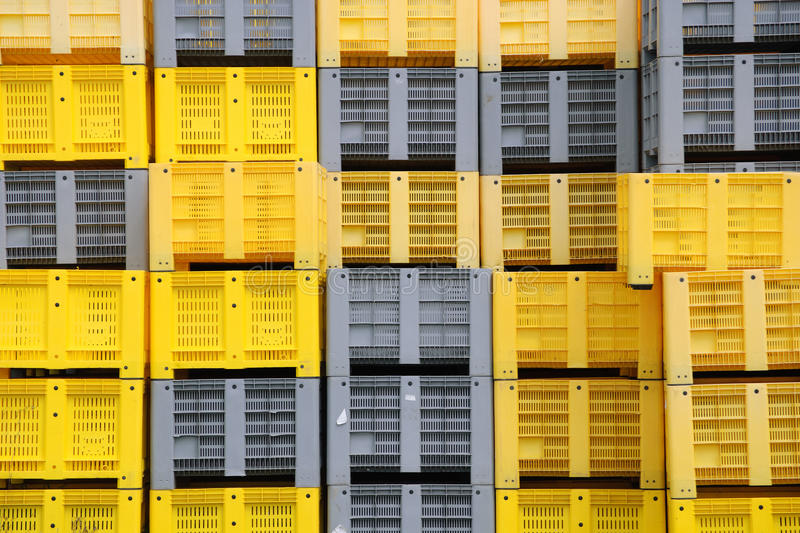 Stacked plastic crates. Yellow and grey colours stock photos