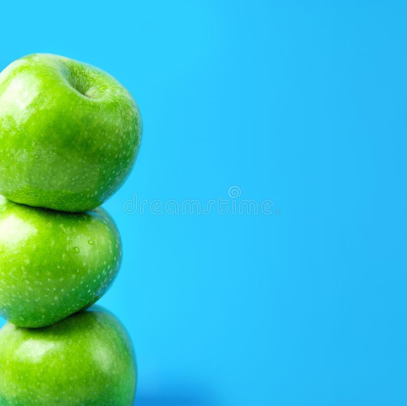 Stacked ripe green organic apples on blue background. Vegan food weight loss detox vitamins plant based diet concept stock image