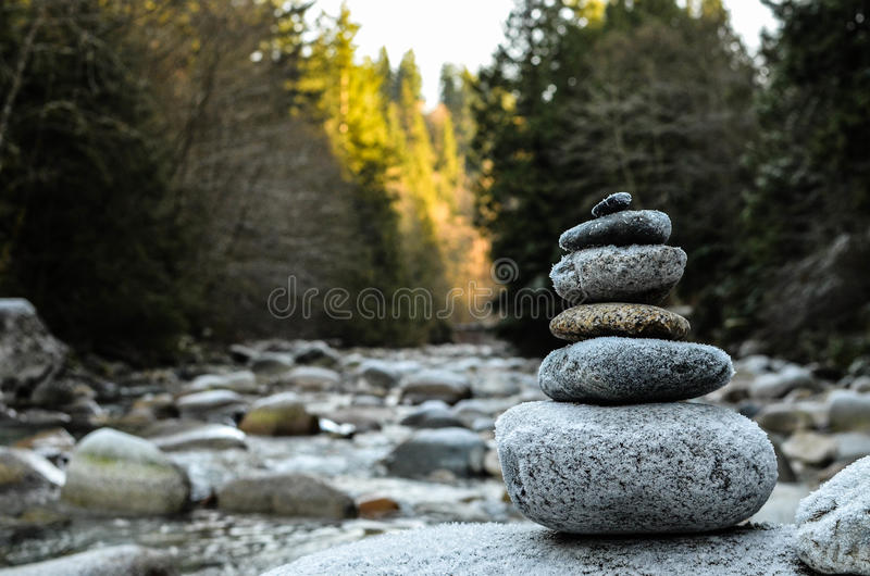 Zen stones stacked on river scene. Stacked rocks showing signs of frost by the river in North Vancouver stock images