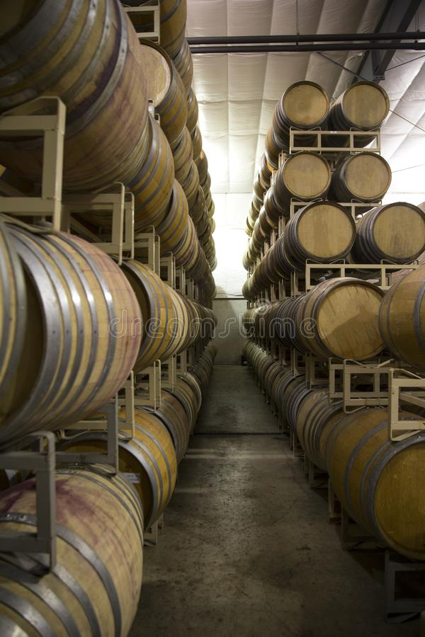 Stacked Rows of French Oak Wine Barrels. Vertical Close Up Front three-Quarter View, 5-High Stacked Rows of French Oak Wine Barrels, Cases of Wine in Background stock photo