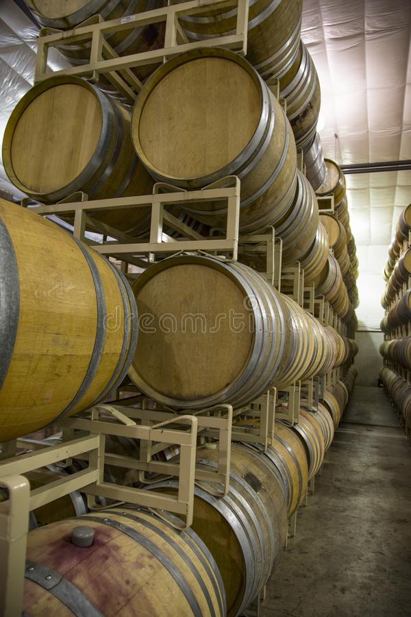 Stacked Rows French Oak Wine Barrels. Vertical Close Up Front three-Quarter View, 5-High Row Stacked French Oak Wine Barrels, Cases of Wine in Background, Clean stock images