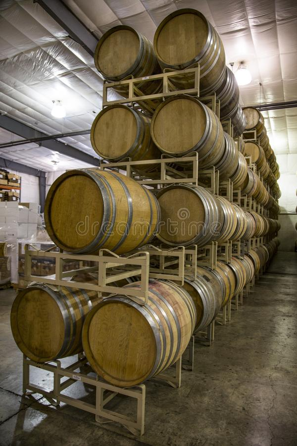 Stacked Rows French Oak Wine Barrels. Vertical Front three-Quarter View,5-High Stacked Rows French Oak Wine Barrels, Cases of Wine in Background, Clean stock image
