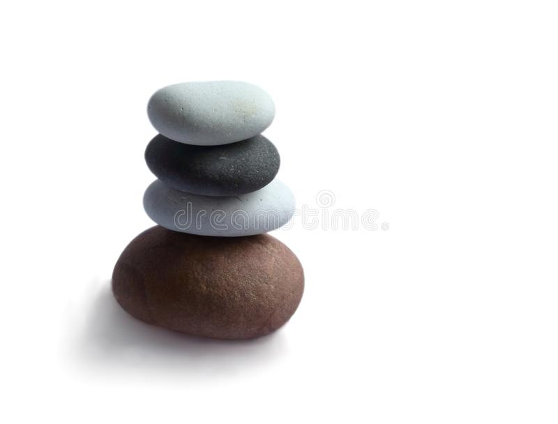 Stacked sea stones pyramids on white background stock photos