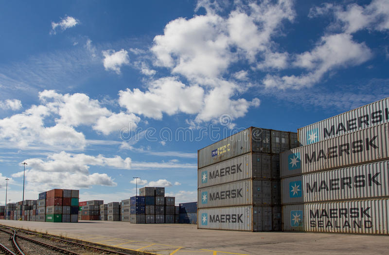 Stacked Shipping Containers. Cargo and shipping containers stacked high in a freight port waiting to be loaded onto goods trains ready for onward movement for stock image