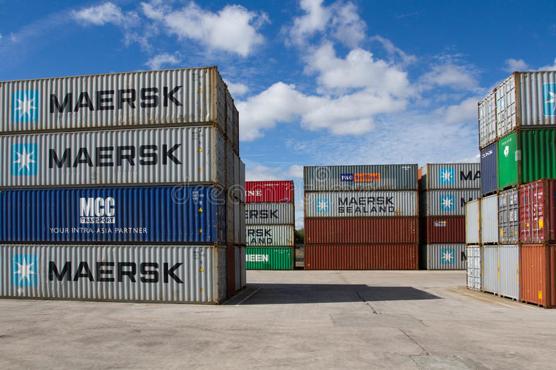 Stacked Shipping Containers. Cargo and shipping containers stacked high in a freight port waiting to be loaded onto goods trains ready for onward movement for stock photography
