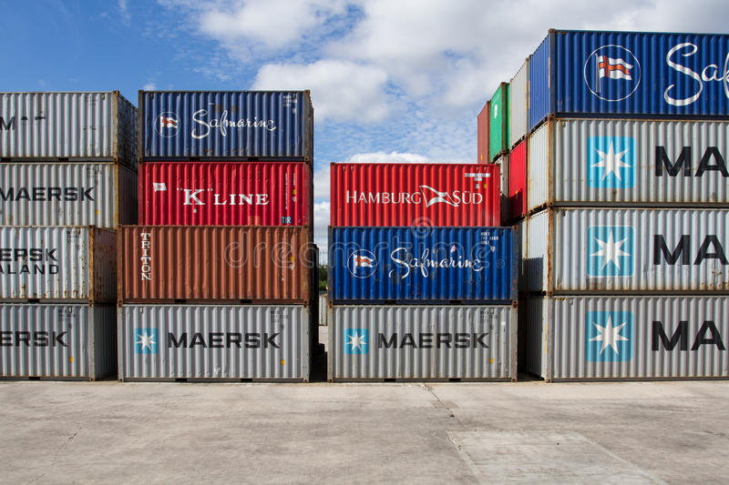 Stacked Shipping Containers. Cargo and shipping containers stacked high in a freight port waiting to be loaded onto goods trains ready for onward movement for royalty free stock photography