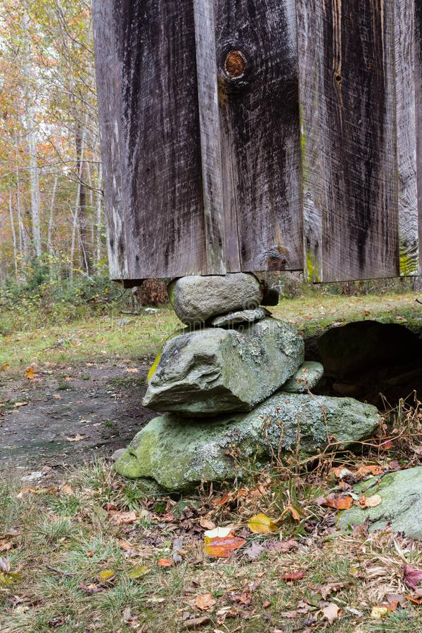 Stacked stone foundation pier beneath a board and batten wall royalty free stock photos