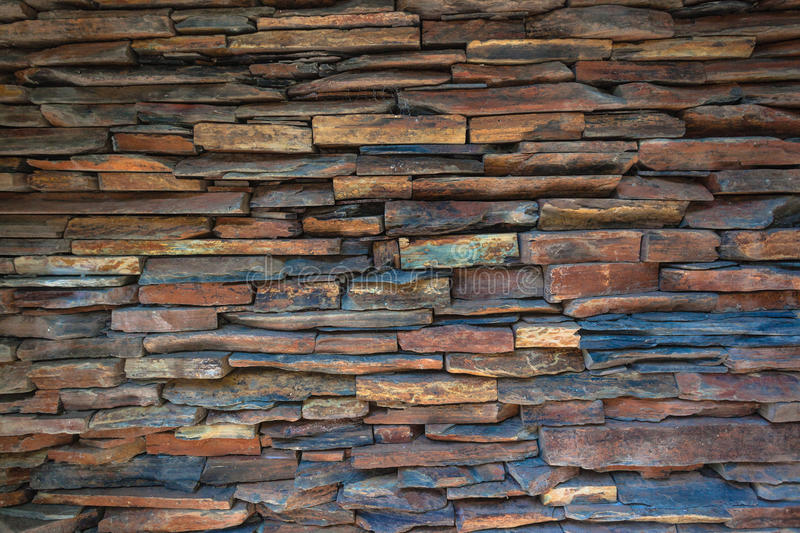 Stacked Stone Slate Wall. The stone slate pieces of earth tone colors in constructed wall a unique art decor feature stock photo