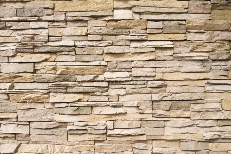 Stacked stone wall background horizontal. Background of a contemporary stacked stone wall in warm brown tones royalty free stock photo