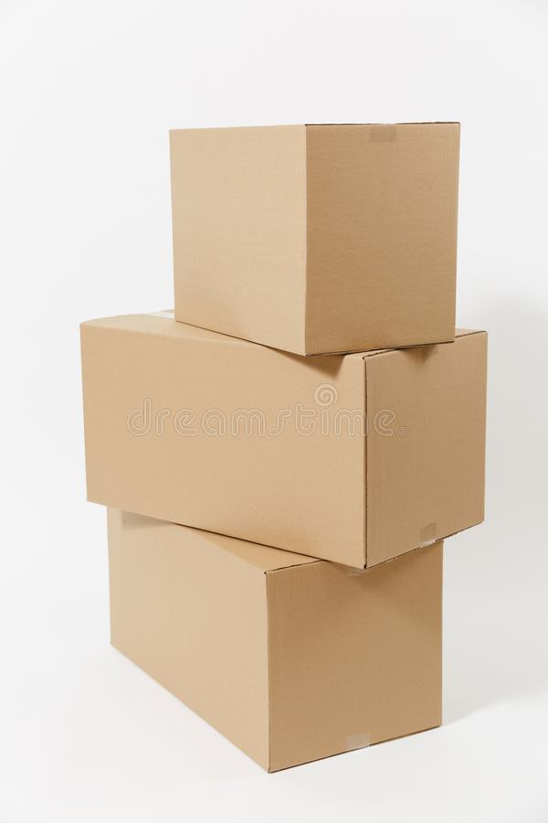 Stacked of three brown clear empty blank cardboard boxes isolated on white background. Receiving package. Copy space for. Advertisement. With place for text royalty free stock photo