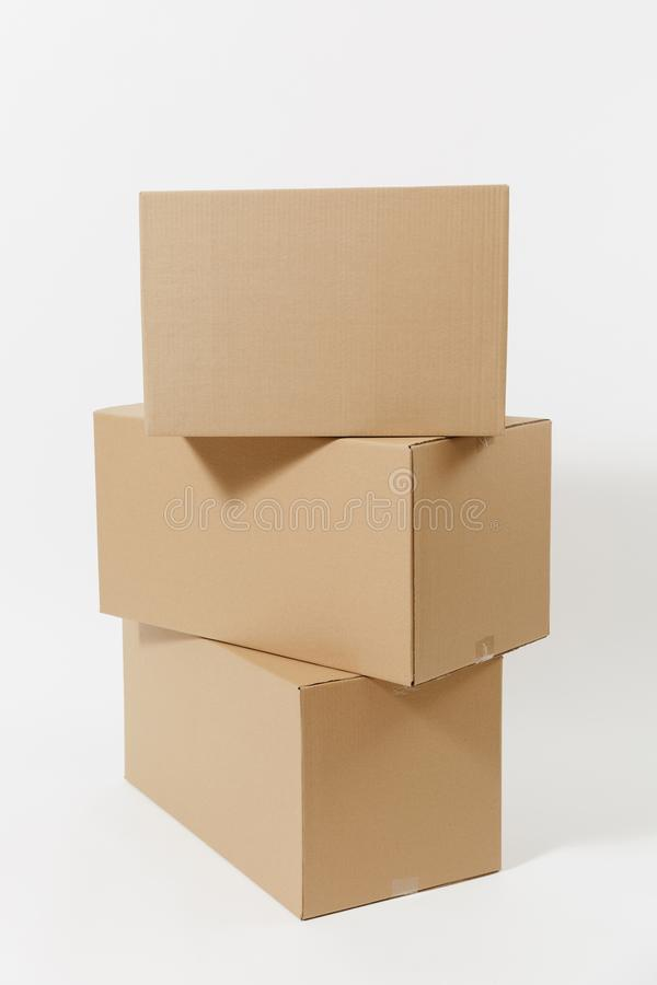 Stacked of three brown clear empty blank cardboard boxes isolated on white background. Receiving package. Copy space for. Advertisement. With place for text stock photos