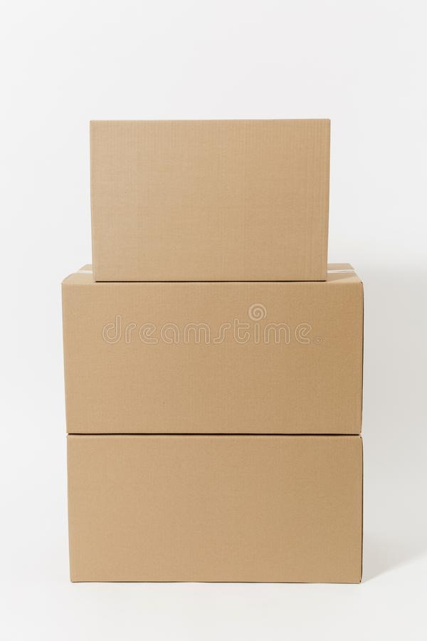 Stacked of three brown clear empty blank cardboard boxes isolated on white background. Receiving package. Copy space for. Advertisement. With place for text royalty free stock images