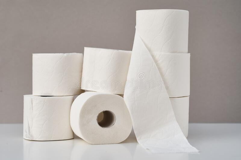 Stacked toilet paper rolls on a gray background. Hygiene concept royalty free stock photos